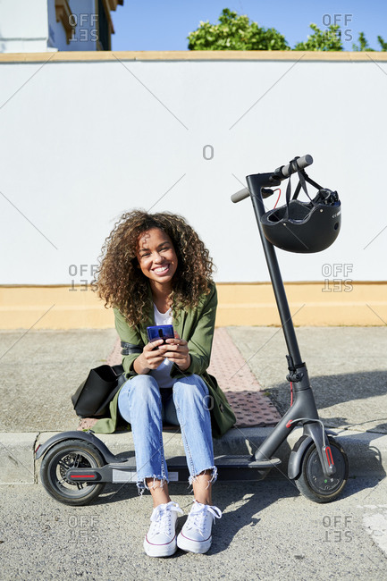 Happy young woman holding smart phone while sitting on sidewalk with electric push scooter
