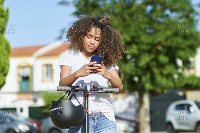 Woman using smart phone while standing with electric push scooter during sunny day