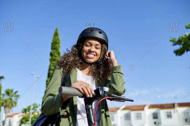 Happy young woman standing with electric push scooter against clear blue sky during sunny day
