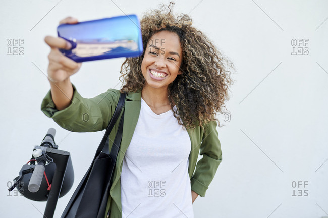 Happy woman taking selfie through smart phone against white wall