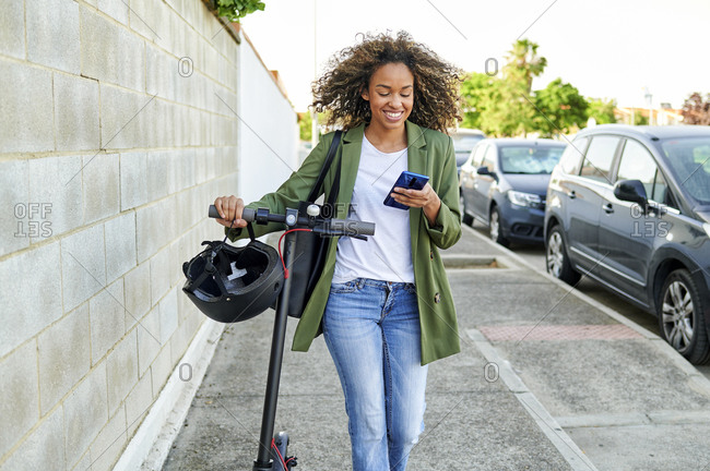 Happy young woman using smart phone while walking with electric push scooter on sidewalk