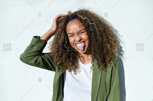 Playful woman sticking out tongue against white wall during sunny day