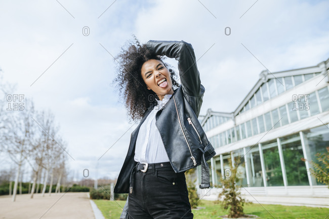 Cheerful young woman sticking out tongue while standing against sky