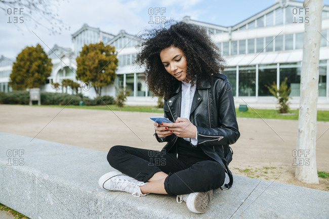 Young afro woman using smart phone while sitting cross-legged on retaining wall