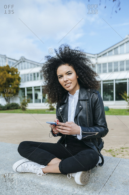 Young woman with afro hairstyle using smart phone while sitting cross-legged on retaining wall