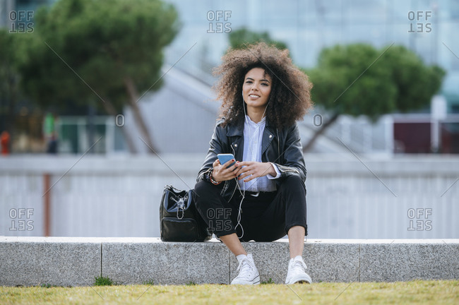 Smiling young afro woman sitting with smart phone and purse on retaining wall