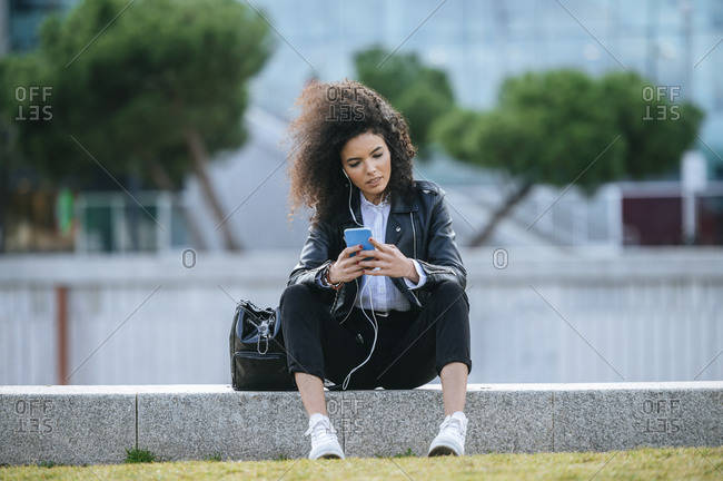 Young woman with afro hairstyle using smart phone while sitting on retaining wall