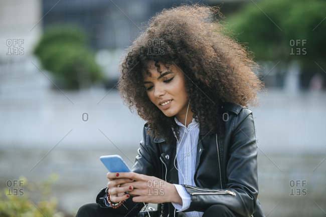 Young afro woman surfing internet on smart phone