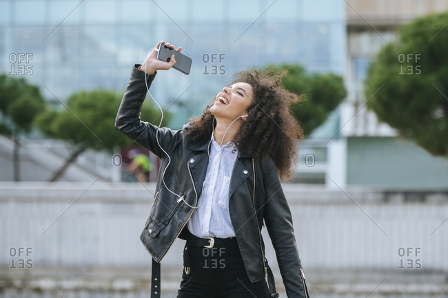 Cheerful young woman with afro hairstyle enjoying while dancing and listening music
