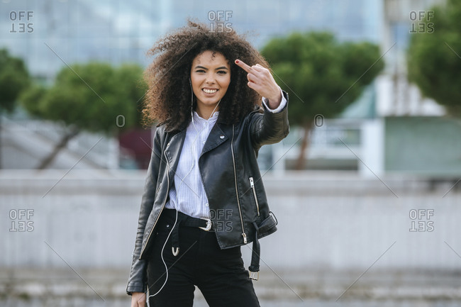 Happy young woman showing middle finger while standing outdoors