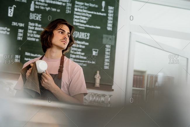 Barista cleaning coffee cup looking away while standing in cafe