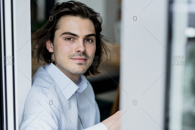 Close-up of handsome businessman looking through window while sitting in cafe