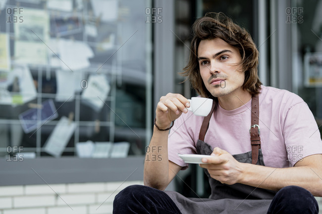 Thoughtful male barista holding coffee sitting outside coffee shop