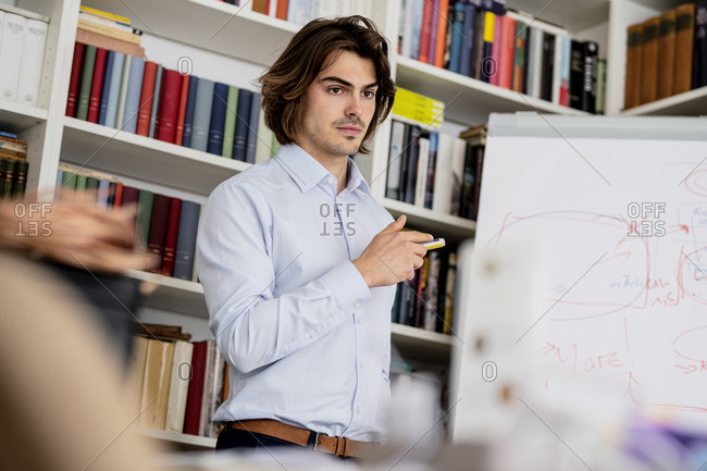 Confident male professional explaining data over whiteboard in meeting at office