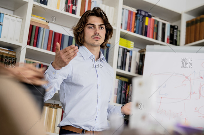 Confident male professional explaining in meeting at office
