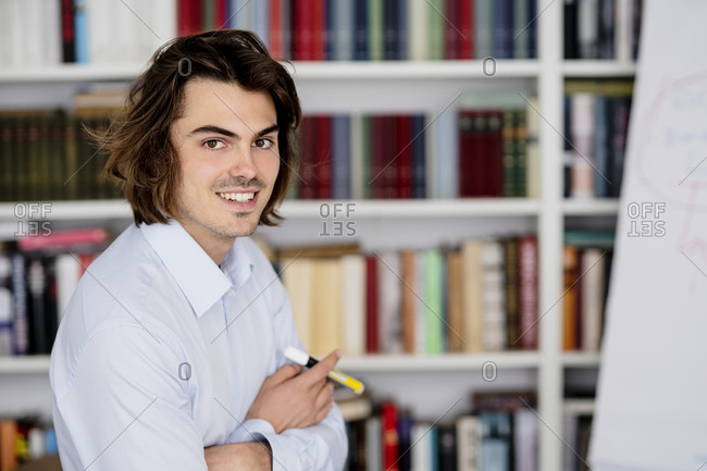 Smiling businessman with arms crossed sitting against bookshelf in office