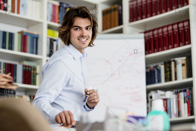 Smiling male professional explaining in meeting at office