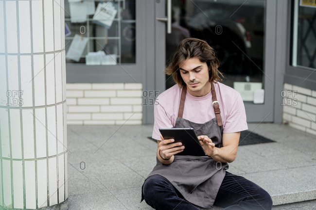Male barista using digital tablet while sitting outside coffee shop