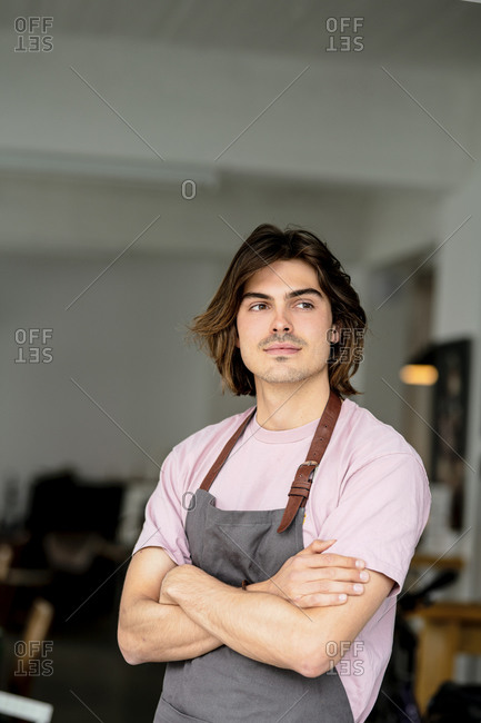 Thoughtful male barista with arms crossed standing in coffee shop
