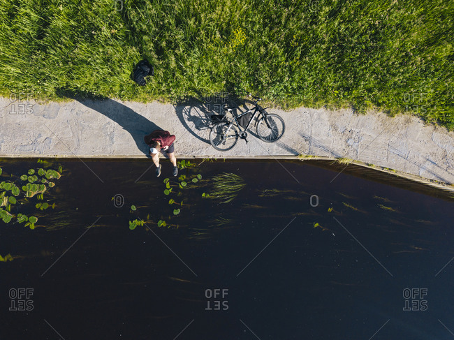 Aerial view of mid adult man with bicycle sitting at river coast during sunny day