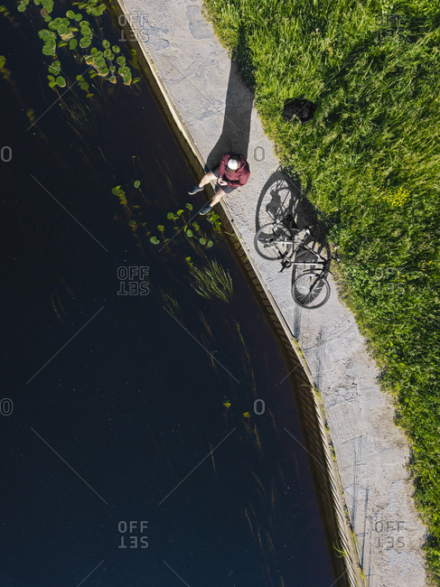 Aerial view of mid adult man with bicycle sitting at river coast in summer