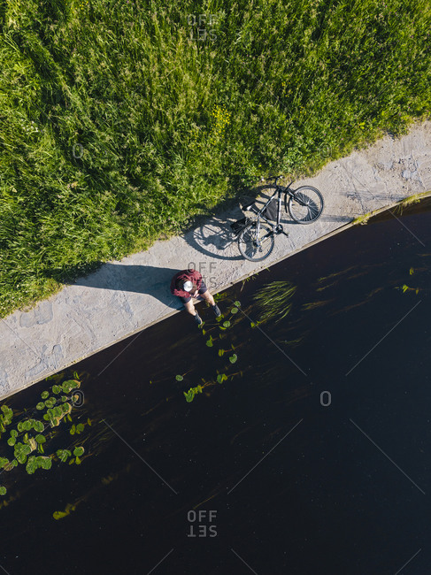 Aerial view of mid adult man with bicycle sitting at river coast