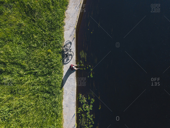 Drone shot of man with bicycle sitting at river coast during sunny day