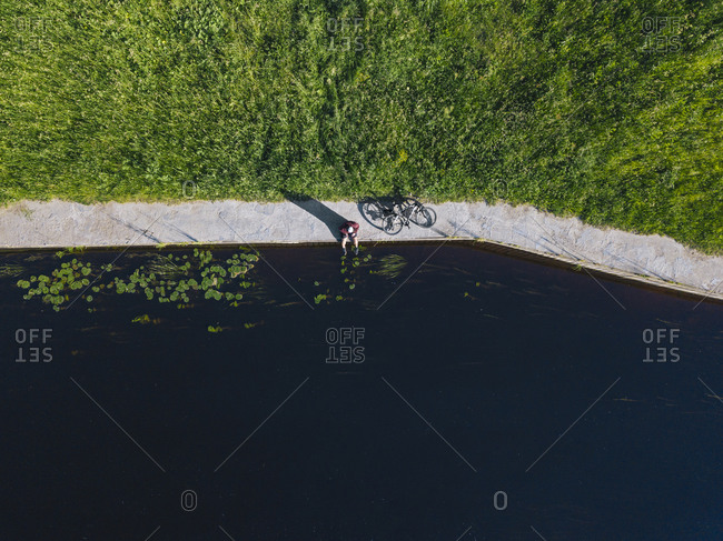 Drone shot of mid adult man with bicycle sitting at river coast