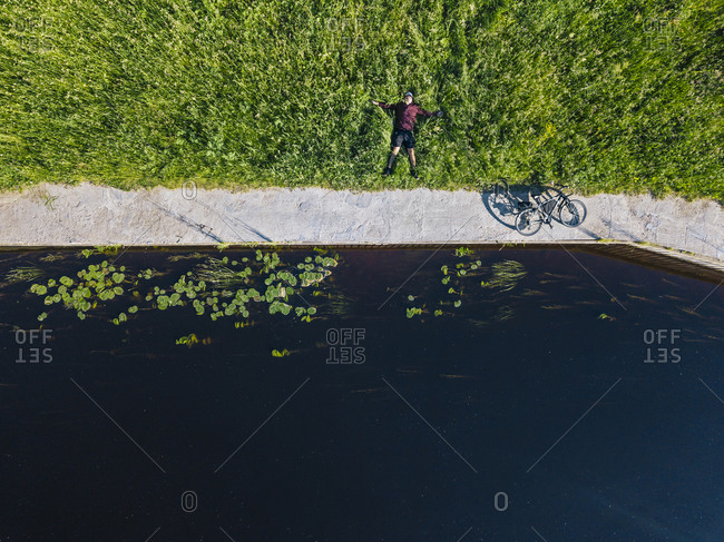 Drone shot of mid adult man with bicycle lying on grassy land at river coast