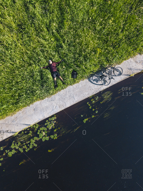 Aerial view of mid adult man with bicycle lying on grassy land at river coast