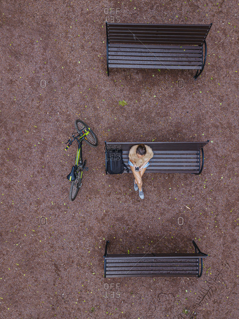 Aerial view of woman using smart phone while sitting on bench in park