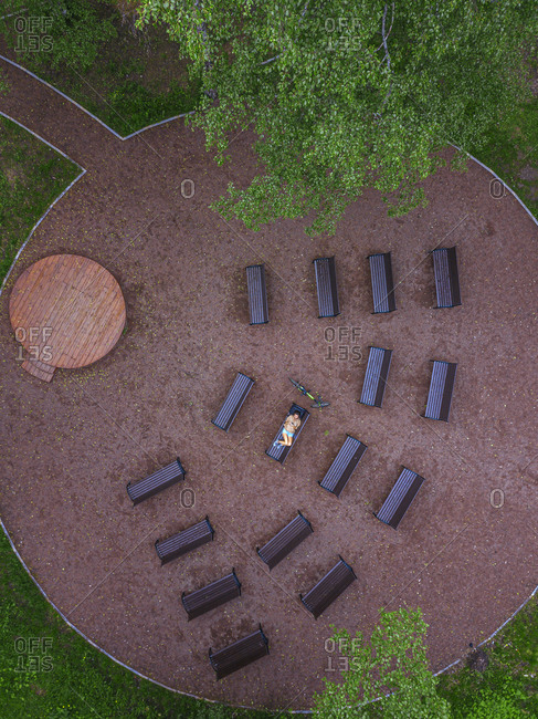 Aerial view of woman lying down on bench in park