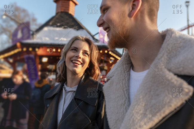 Close-up of happy young couple talking while standing in amusement park at sunset