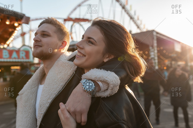 Close-up of young man with hand on girlfriend's shoulder standing in amusement park at sunset
