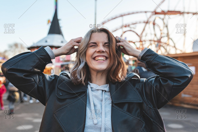 Close-up of cheerful young woman with hands in hair standing at amusement park during sunset