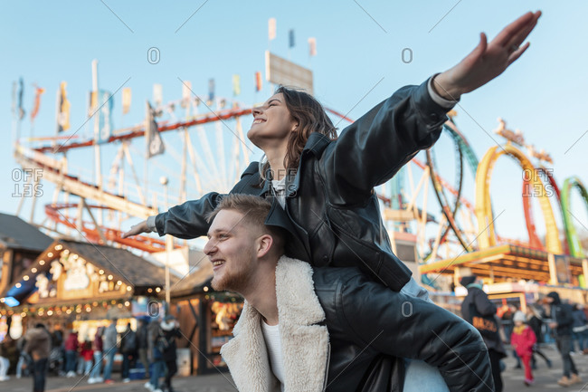Happy man piggybacking carefree girlfriend while standing at amusement park
