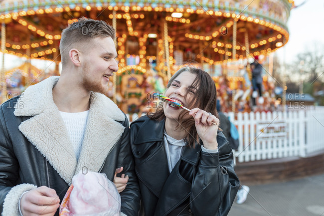 Happy man looking at girlfriend eating lollipop at amusement park