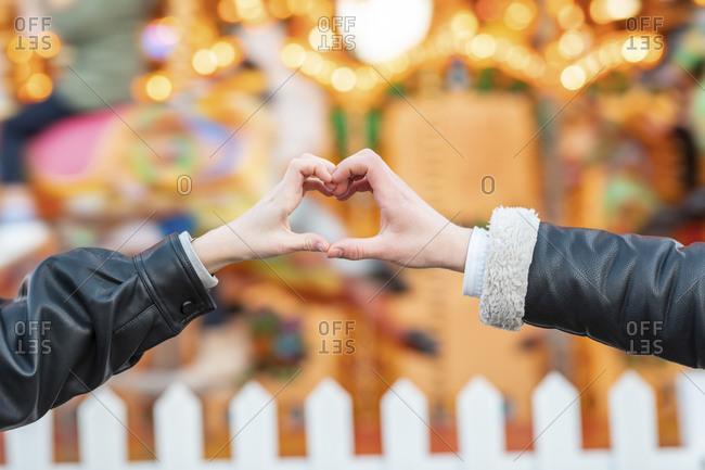 Close-up of couple hands making heart shape at amusement park