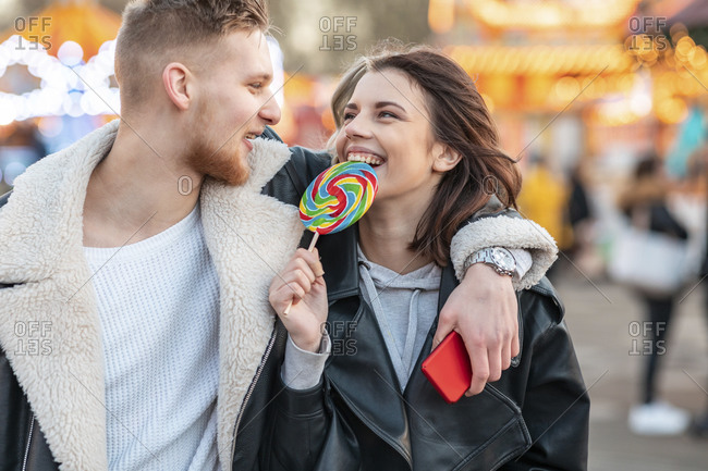 Happy woman looking at boyfriend while eating lollipop at amusement park