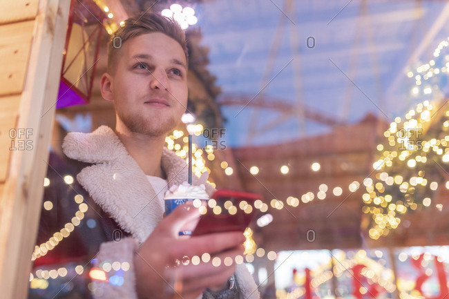Man holding hot chocolate and smart phone looking through window in store at amusement park