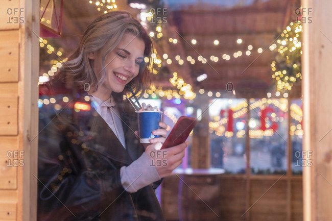 Smiling woman holding hot chocolate using smart phone in store at amusement park seen through window