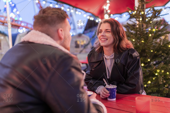 Smiling woman talking with boyfriend while sitting at amusement park
