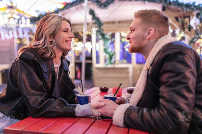 Romantic couple holding hands at table while sitting in amusement park