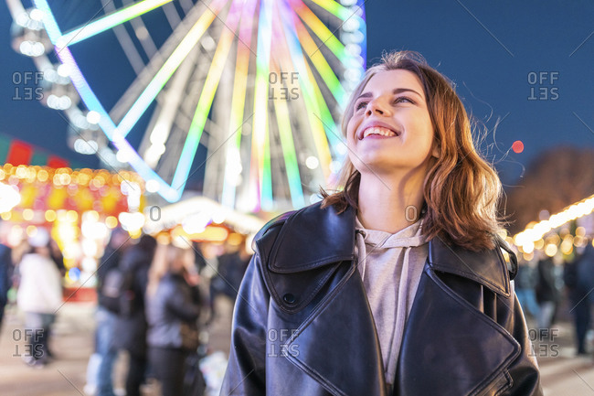 Close-up of smiling young woman looking up while standing in amusement park at night
