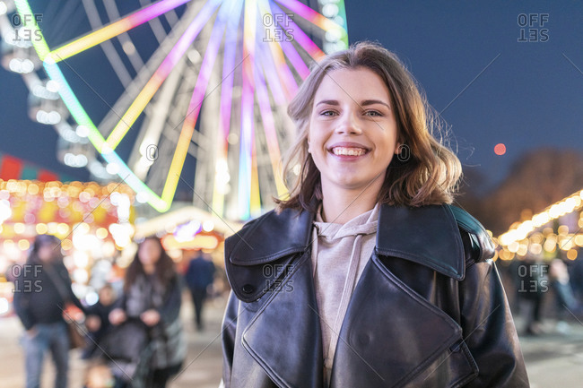 Close-up of smiling young woman standing in amusement park at night
