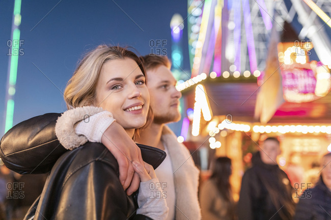 Smiling woman with boyfriend standing in amusement park at night