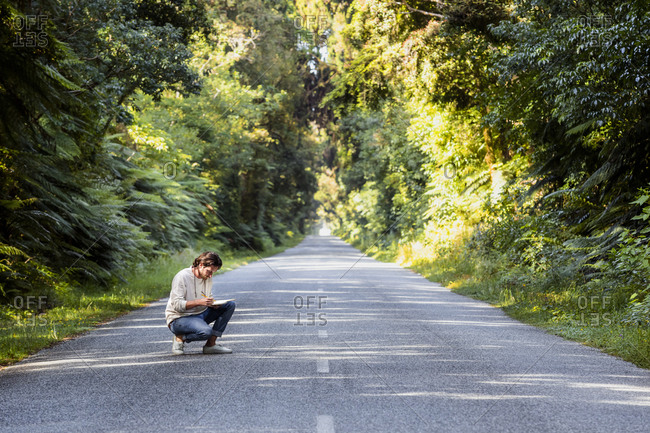 Young man writing in diary while crouching on country road amidst trees