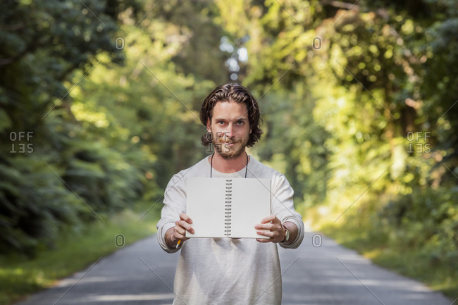Confident young man showing blank book while standing on road in forest