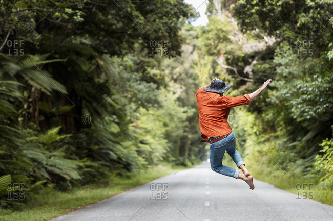 Excited man jumping on country road amidst trees in forest