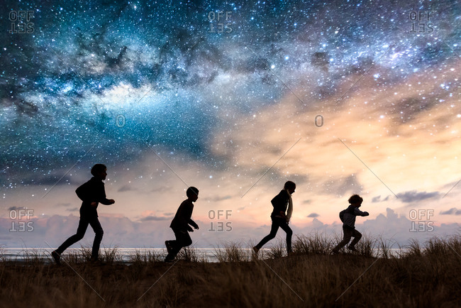 Children running in tall grass against a surreal night sky